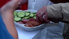 Tourists eat cucumbers and sausage Stock Footage