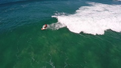 Aerial view of a man sup stand-up paddleboard surfing in Hawaii, slow motion. Stock Footage