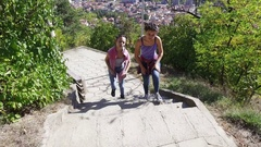 Two young teen girls in the forest running up stairs and having fun smiling Stock Footage