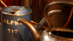 Pull focus shot of two vintage oil buckets next to a working steam engine Stock Footage