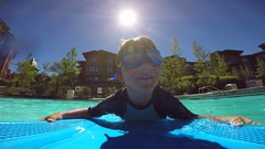 POV of a boy playing on a body board in a pool at a hotel resort, super slow mot Stock Footage
