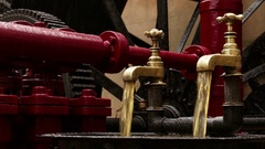 Closeup shot of two industrial faucets pouring oil on an hydraulic engine Stock Footage