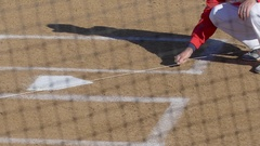 A baseball player prepares the field by painting the base lines white before a g Stock Footage