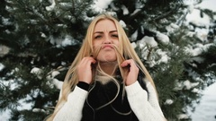 Funny woman fools around in pine winter snowy forest outdoors Stock Footage