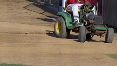 A baseball player drives a tractor to prepare the infield a game. Stock Footage
