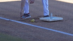 A baseball player installs first base before a game. Stock Footage