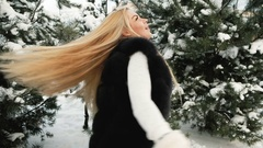 Fantastic blonde is turned against background of snow covered pines Stock Footage