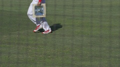 A baseball player installs first base before a game, slow motion. Stock Footage