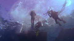 A group of scubadivers jumping into the water with a dive bot and sink to the Stock Footage