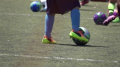 Details of a ball and players at a youth soccer football camp on a turf field. Stock Footage