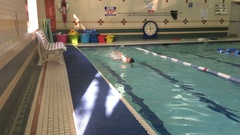 A boy swims freestyle during swimming lessons in a pool. Stock Footage