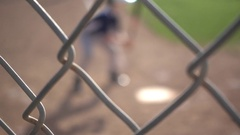 Boys playing in a little league baseball game through a chain-link fence. Stock Footage