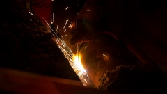 A man is welding two heating system pipes together Stock Footage