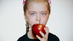 Sad little girl eats a red apple Stock Footage
