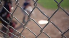 Boys playing in a little league baseball game through a chain-link fence, super Stock Footage