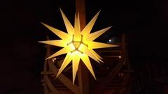 Close-up of swinging Christmas Yellow star of Bethlehem. Stock Footage