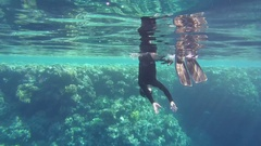 Videographer, diver dives into the depths of a video camera mounted   Stock Footage