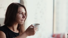 Close-up of a pretty brunette womans face having a cup of coffee or tea. Stock Footage