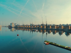 Aerial view of East London docklands and the Thames on a day of a clear blue sky Stock Footage