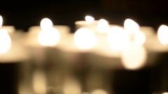 Lots of candles burning in the dark. Defocusing. White light, bokeh Stock Footage