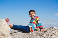 Boy sitting on a rock holding up his feet Stock Photos