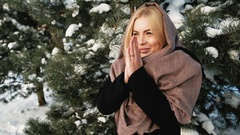 Beautiful woman heats hands, snow covered coniferous forest Stock Footage
