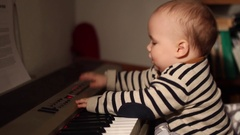 Home movies of a baby in a family wearing a striped sweater to match a piano. Stock Footage