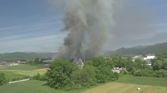 AERIAL: People trying to put out the fire in burning factory in countryside Stock Footage