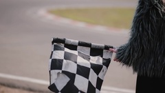 Back view of a woman is holding a waving race checkerd flag. Go-kart track Stock Footage