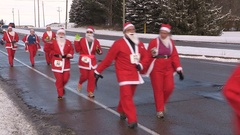 Runners dressed as santa claus in marathon style run through the city Stock Footage