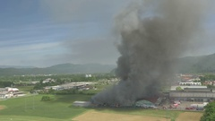 AERIAL: Firefighters extinguishing hot fire in burning agricultural factory Stock Footage