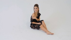 Young European woman in black lingerie on photo session in the studio Stock Footage