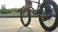 SLOW MOTION CLOSE UP: Unrecognizable man riding bmx bike at golden summer sunset Stock Footage