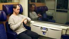 Man using his smartwatch in a train. Modern wearable device technology. 4K video Stock Footage