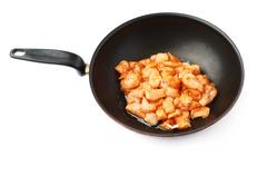 Raw chicken fillet cutted into pieces and spiced in black pan isolated over Stock Photos