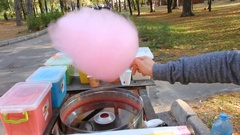 Making pink cotton candy in candy floss machine. Making candy floss in the park Stock Footage
