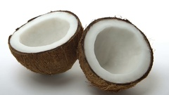 Ripe tropical coconut split in two halves rotating on white background. Looping Stock Footage