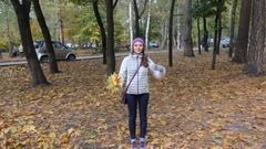 Young woman with sheaf of leaves walking in the autumn park and smiling Stock Footage