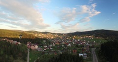 Rising up over a small town in the forest valley Stock Footage