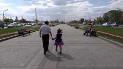 Father with little girl go, then run forward at empty promenade, follow camera Stock Footage