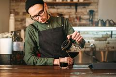 Barman pours coffee in a glass. Stock Photos