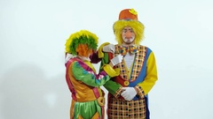 Portrait of a couple of circus clowns having fun together against white Stock Footage