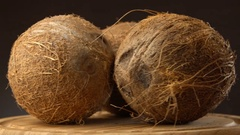 Three ripe tropical coconuts rotating on a wooden table against black background Stock Footage