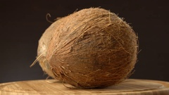 Two ripe tropical coconuts rotating on a wooden table against black background Stock Footage
