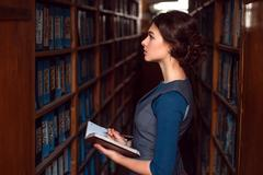 Girl with notebook select textbook in library. Stock Photos