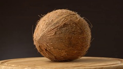 Ripe tropical coconut rotating on a wooden table against black background Stock Footage