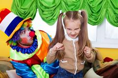 Child girl and clown playing on birthday party. Stock Photos