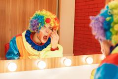Clown does a make-up in front of the mirror. Kuvituskuvat