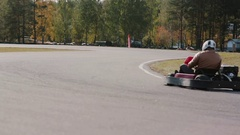 Two drivers on a go-kart track pass by the camera. Go-kart race Stock Footage