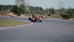Two drivers on a go-kart track move into the camera and pass it by. Go-kart race Stock Footage